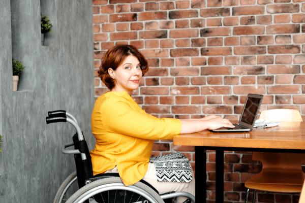 jeunne femme en situation de handicap devant un ordinateur à l'école