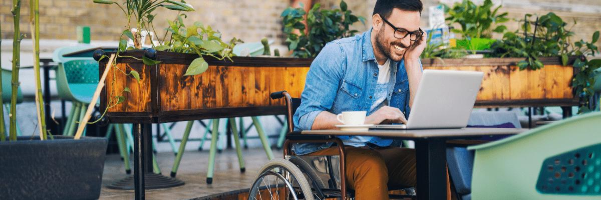 homme handicapé en fauteuil roulant devant un ordinateur