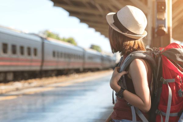 jeune femme attendant un train avec un sac à dos